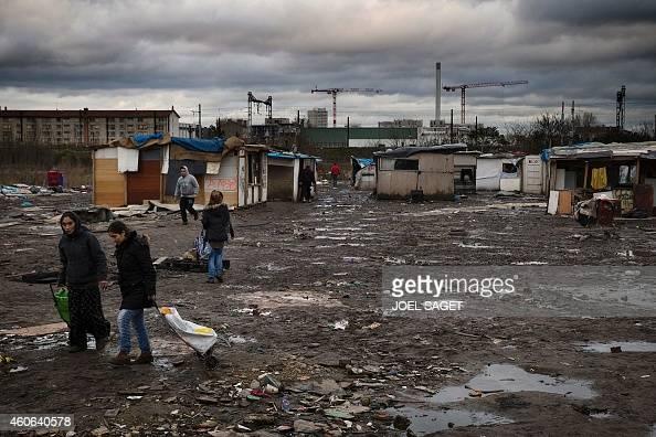Women walk through a Roma camp in IvrysurSeine southern Paris on December 18 2014 A former gendarmerie in IvrysurSeine has been renovated to host 11...
