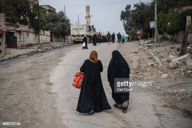 Women walk to a Shia volunteer food distribution point during fighting against Islamic State in west Mosul on April 12 2017 in Mosul Iraq Despite...