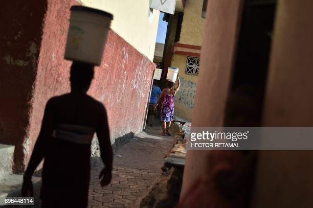 Women walk with buckets of water on their heads on the streets of Jalousie neighborhood in the commune of Petion Ville PortauPrince on June 20 2017 /...