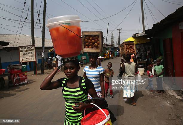 Women walk with their wares through the West Point slum on February 9 2016 in Monrovia Liberia West Point the most impoverished and overpopulated...