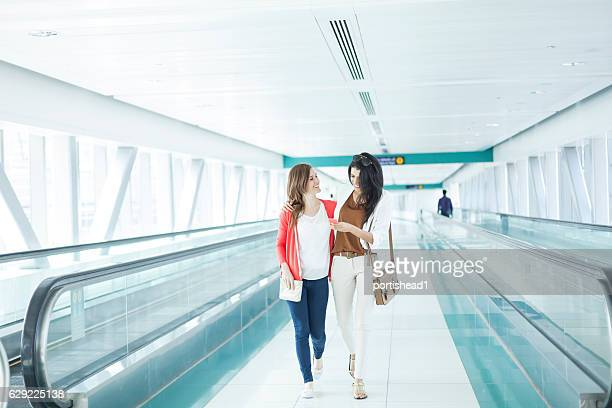Women walking and using smart phone at airport