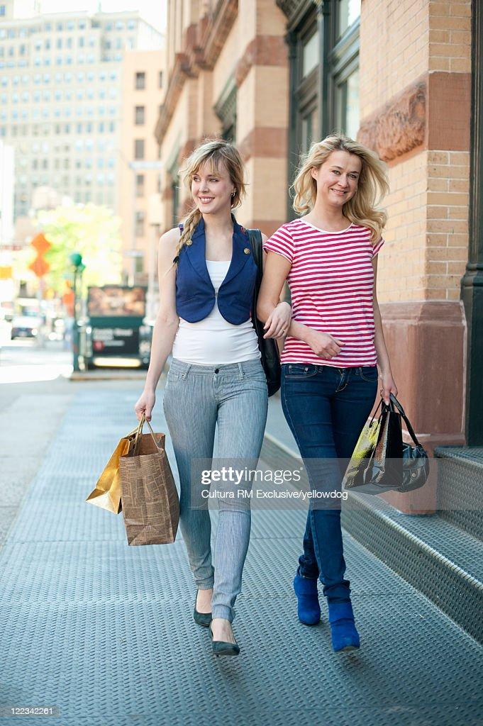 Women walking arm-in-arm on city street : Stock Photo