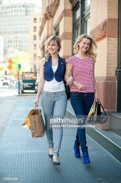 Women walking arm-in-arm on city street