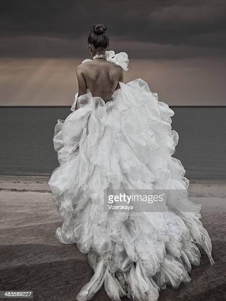 Frau zu Fuß am Strand in Plastiktüte-Kleid