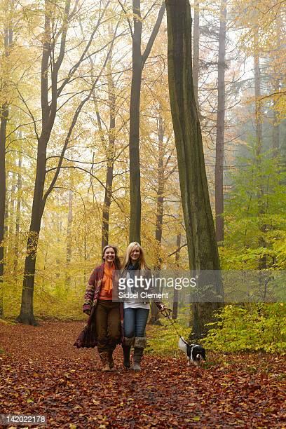 Women walking dog in forest