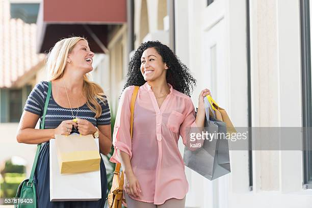 Women walking down street  carrying shopping bags
