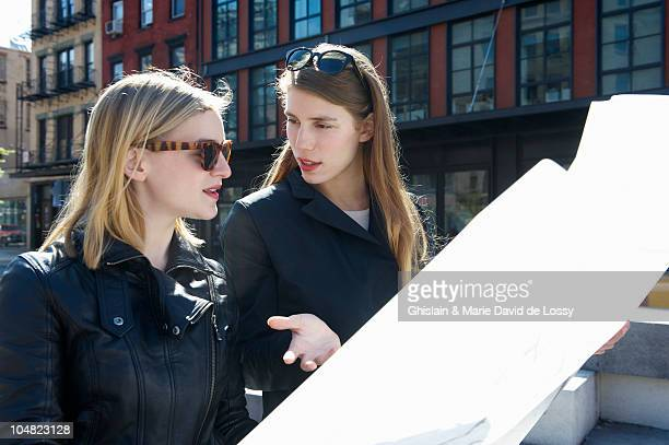 Women walking in the street with a map