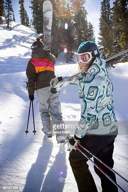 Women walking up mountain carrying skis