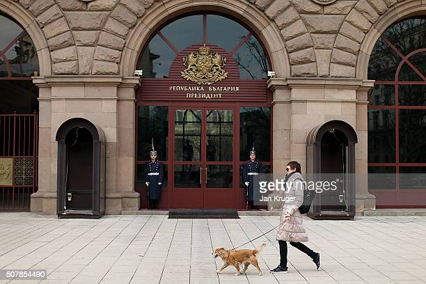 A women walks her dog past guards at the entrance to the Presidencial Palace on January 31 2016 in Sofia Bulgaria