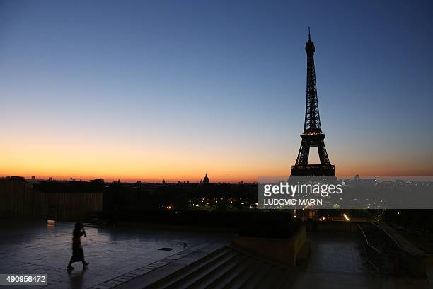 A women walks on the Trocadero Plaza opposite the Eiffel tower at sunrise on October 1 2015 AFP PHOTO / LUDOVIC MARIN