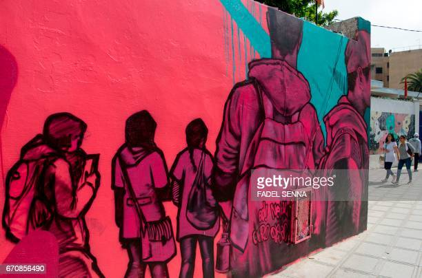 Women walks past a mural during the 'Jidar' street art festival in the capital Rabat on April 20 2017 / AFP PHOTO / FADEL SENNA