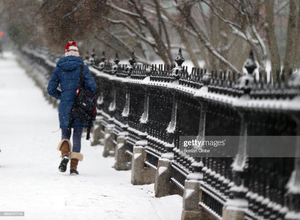 A women walks past the Boston Public Garden in Boston as a winter storm arrives in the region on Mar. 14, 2017.