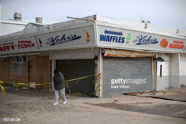 A women walks past the closed boardwalk that was damaged by Superstorm Sandy February 19 2013 in Seaside Heights New Jersey Governor Chris Christie...