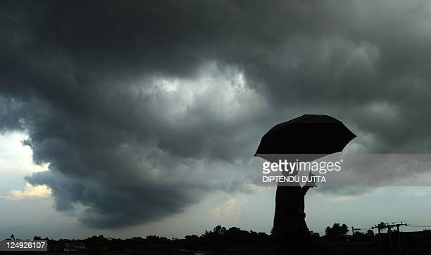 A women walks with an umbrella as monsoon clouds cover part of the sky in Matigara village on the outskirts of Siliguri on September 142011 India has...