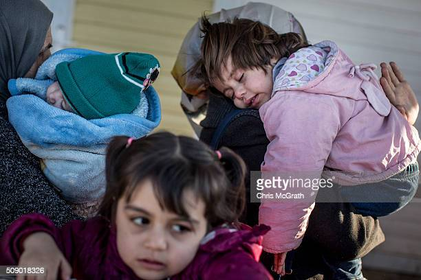 Women wanting to leave Turkey carry their children as they wait in line to pass through the border gate as a small number of Syrian refugees were...