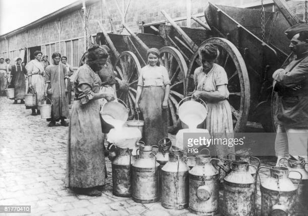 Women war workers filling churns with milk at a distribution centre outside Paris France circa 1916