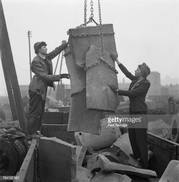Women war workers Violet Wilson and Marjorie Pearson loading up scrap metal ready to be broken up at a major steeel works in Britain 25th March 1942...