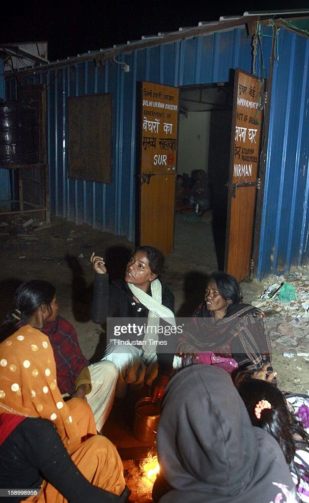 Women warm themselves around the fire as temperature dips below normal, before sleeping at night shelter at Urdu park in Near Jama Masjid on January 4, 2013 in New Delhi, India. Delhi continued to shiver at a minimum of 2.9 degrees, four notches below normal. Over a 175 people have died so far in the bitter cold in Northern India.