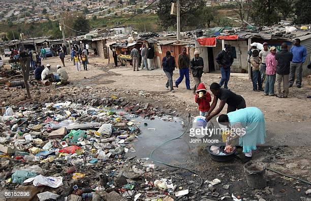 Women wash and a boy drinks from a common water tap near a polling station on April 22 2009 in the Sweetla Squatter Camp near Alexandra Township...