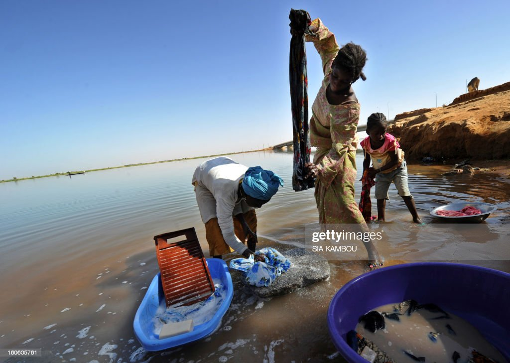 Women wash clothes on the Niger river near the Gao bridge guarded by French soldiers on February 3, 2013 in Gao. France said it carried out major air strikes today near Kidal, the last bastion of armed extremists chased from Mali's desert north in a lightning French-led offensive. AFP PHOTO / SIA KAMBOU