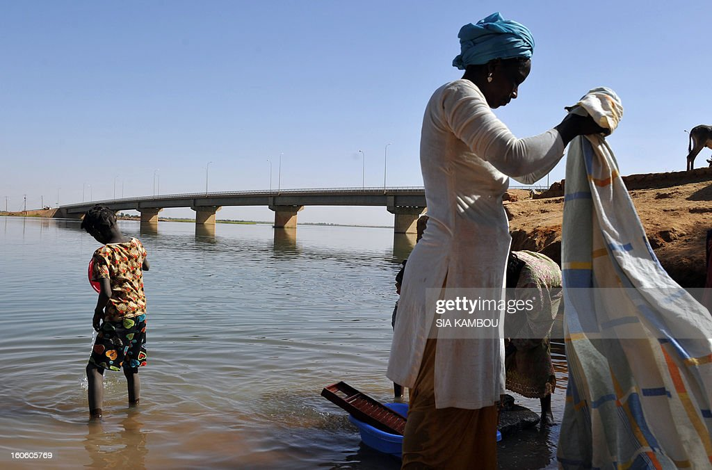 Women wash clothes on the Niger river near the Gao bridge guarded by French soldiers on February 3, 2013 in Gao. France said it carried out major air strikes today near Kidal, the last bastion of armed extremists chased from Mali's desert north in a lightning French-led offensive.