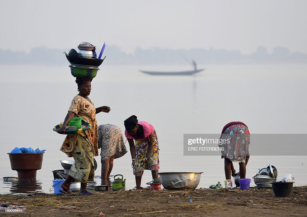 Women wash dishes in the Niger river on January 23, 2013 in Segou 270km north of the capital Bamako.