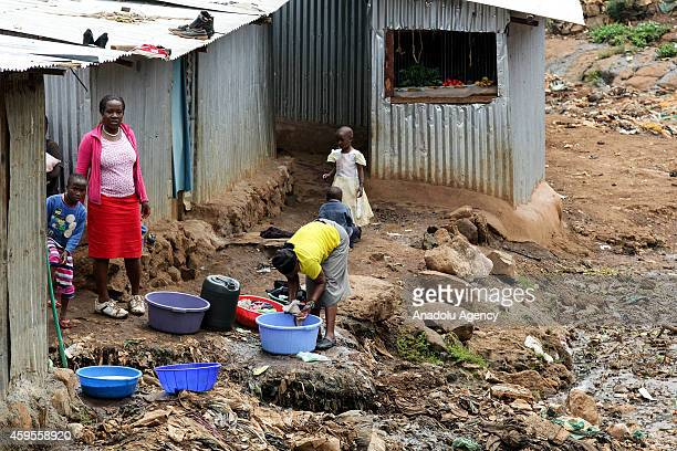 Women wash the clothes outside their shack in Kibera Nairobi Kenya on November 20 2014 They live difficult conditions due to lack of water...