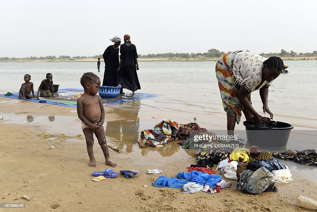 Women wash their clothes in the Chari river near N'Djamena on March 28 2015 AFP PHOTO / PHILIPPE DESMAZES