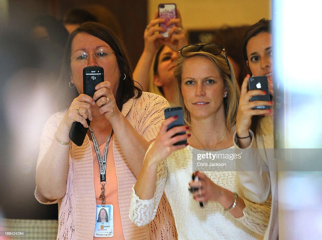 Women watch and take camera phone pictures as HRH Prince Harry tours an anti-landmine photography exhibition by The HALO Trust charity during the first day of his visit to the United States at the Russell Senate Office Building on May 9, 2013 in Washington, DC. HRH will be undertaking engagements on behalf of charities with which the Prince is closely associated on behalf also of HM Government, with a central theme of supporting injured service personnel from the UK and US forces.