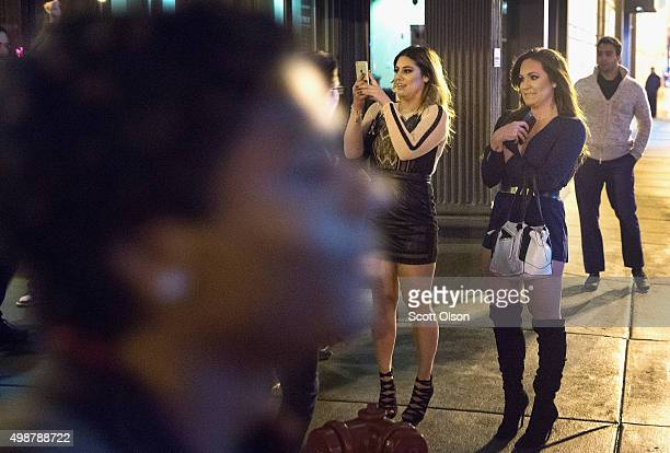 Women watch from outside a bar as demonstrators protesting the death of Laquan McDonald march by on November 25 2015 in Chicago Illinois Small and...