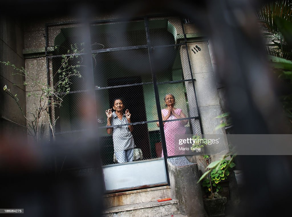 Women watch from their porch as a procession passes near the Nossa Senhora da Penha Church on the final day of the annual October feast of the patron saint marking the 378th anniversary of the church on October 27, 2013 in Rio de Janeiro, Brazil. Pilgrims often climb the entire 382 steps that lead to the church, originally constructed in 1635, which is perched on a rocky hill. Brazil holds more Catholics than any other country.
