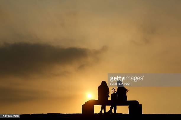 WOmen watch the sunset in the world's oldest port of the historical Lebanese city of Byblos north of the capital Beirut on February 27 2016 / AFP /...
