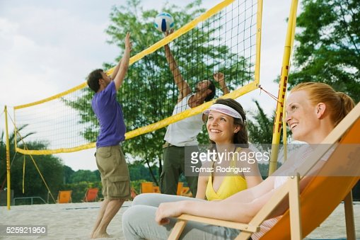 Women Watching a Game of Beach Volleyball : Stock Photo
