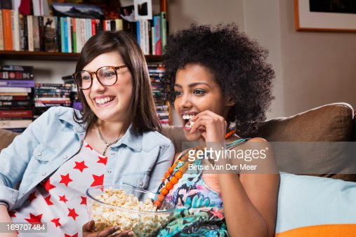 Women watching television in livingroom. : Stock Photo