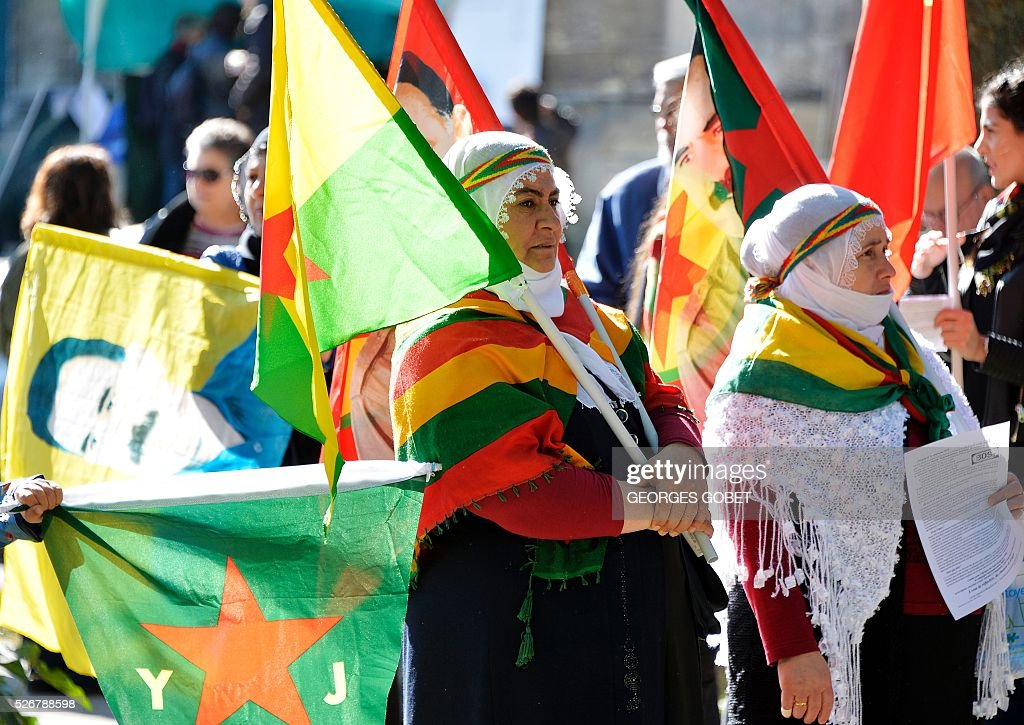 Women wave flags picturing Kurdish Worker Party's (PKK) jailed leader Abdullah Ocalan as they demonstrate in the streets of Bordeaux during the traditional May Day rally on May 1, 2016. / AFP / GEORGES