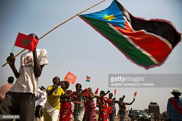 Women wave Moroccan and South Sudan flags during a welcoming ceremony for The King of Morocco on February 1 at Juba airport at the start of his two...