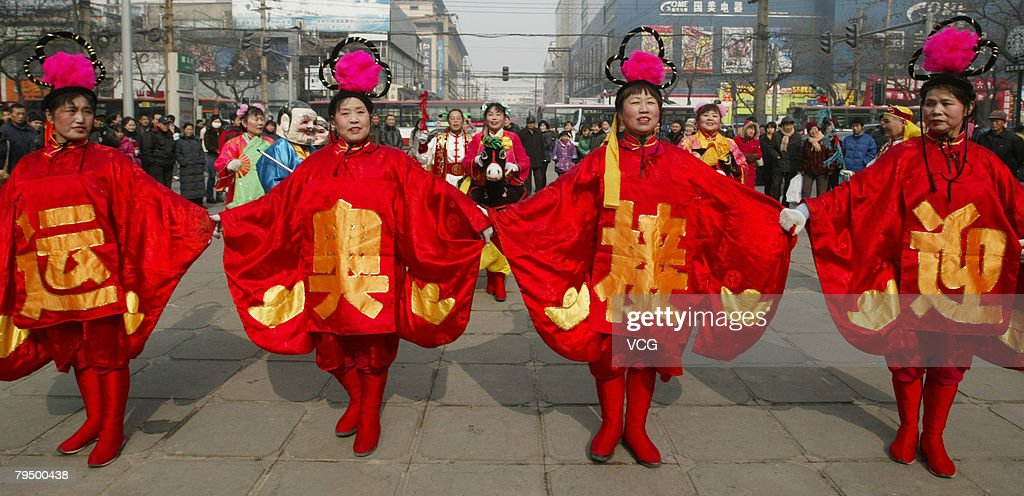 Women wear costumes displaying Chinese characters giving good wishes for Beijing 2008 Olympic Games, February 3, 2008, in Xian, Shaanxi Province, China.