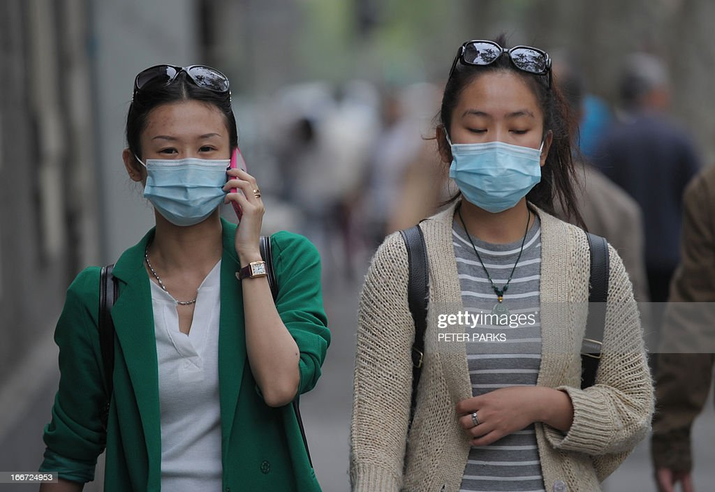 Women wear face masks on a street in Shanghai on April 16 2013 as China's H7N9 bird flu virus spreads further afield In total nationwide 62 people...