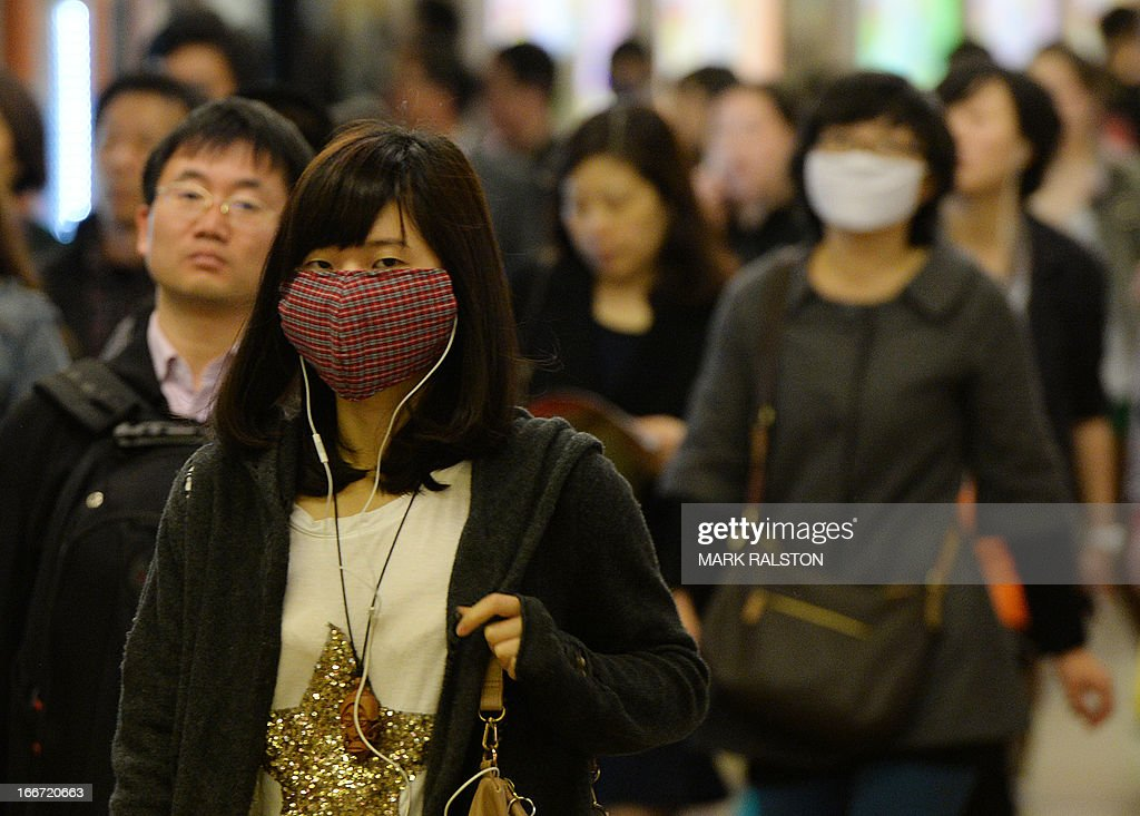 Women wear facemasks as the city's commuters protect themselves against the H7N9 bird flu virus in the downtown area of Shanghai on April 16, 2013. Chinese state media on April 15 urged people to keep eating chicken and help revive the poultry industry, which lost 1.6 billion USD in the week after the H7N9 bird flu virus began infecting humans and a total of 63 people have been confirmed as infected and 14 have died in the two weeks. AFP PHOTO / Mark RALSTON
