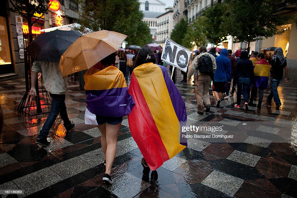 Women wear Republican Flag while raining during a demonstration against the Spanish Monarchy under the header 'Check the King' at Arenal Street on September 28, 2013 in Madrid, Spain. Organizers call for a demonstration on the anniversary of 'Surround the congress protest' to claim the abolition of the Monarchy. Currently King Juan Carlos of Spain is in hospital recovering from a hip operation. The Spanish Royal Family has lost popularity since the King injured his hip on elephant hunting trip and the King's son-in-law, Inaki Urdangarin is being investigated over a corruption scandal.