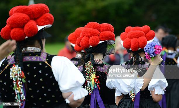 Women wear traditional Black Forest costumes and hats topped with pompoms a socalled Bollenhut during a pageant on the occasion of the 50th...