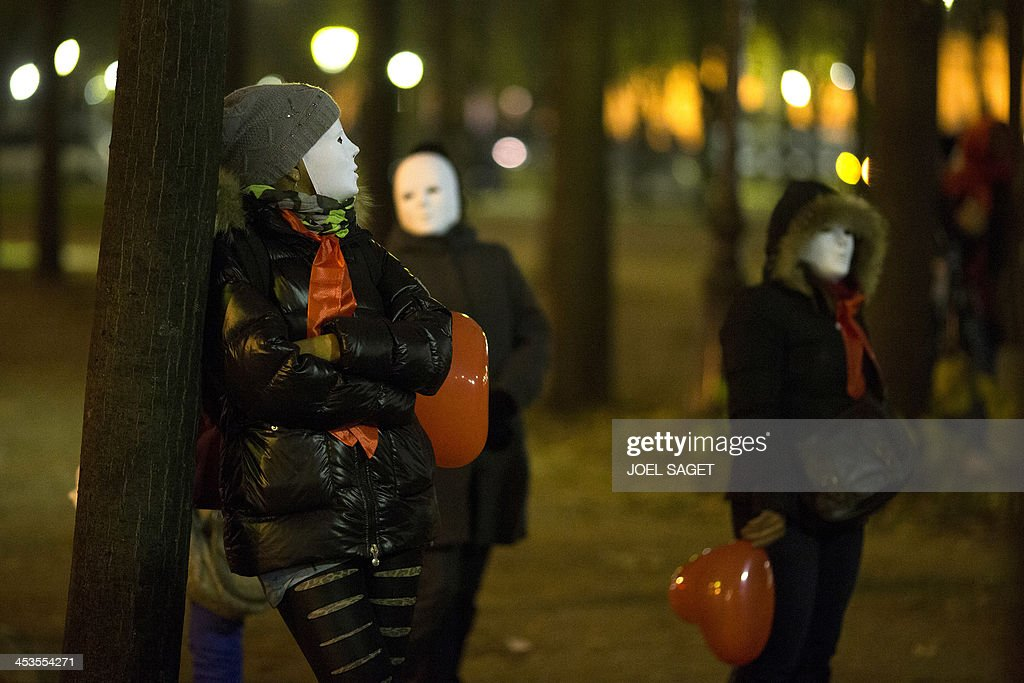 Women wearing a mask take part in a demonstration of sex workers on December 4, 2013 in Paris, after French lawmakers approved today a controversial bill that will make the clients of prostitutes liable for fines starting at 1,500 euros ($2,000).