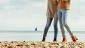 Female autumnal footwear. Women wearing blue jeans and stylish autumn collection boots walking through beach. Shoes perfect for winter.