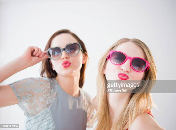 Women wearing colorful sunglasses and lipstick