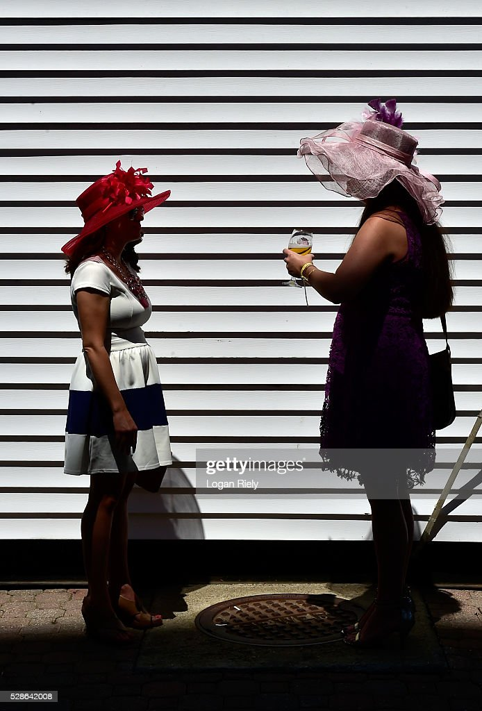 Women wearing festive hats talk prior to the 142nd running of the Kentucky Oaks at Churchill Downs on May 06, 2016 in Louisville, Kentucky.