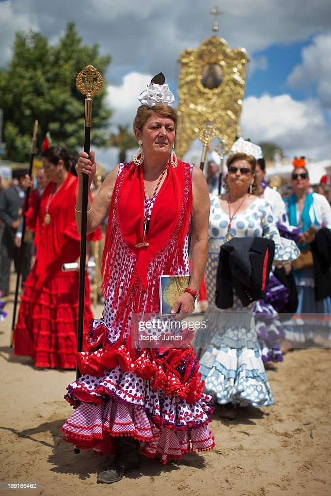Women wearing flamenco dresses walk down the street on May 19, 2013 in El Rocio, Spain. The Romeria del Rocio procession brings together roughly a million pilgrims each year making their way for as long as seven days from throughout Andalusia by foot, on horsebacks and horse drawn carriages, to the doors of the Hermitage of El Rocio. On Sunday night, after reciting the Holy Rosary at candlelight, and the passing of all the simpecados in front of the chapel, with the one from the brotherhood of Matriz de Almonte as the last one, el salto de la reja begins, the jumping of the fence surrounding the Hermitage after which the Virgin of El Rocio is carried out onto the sandy streets of the small town for the 'Blanca Paloma' procession. Then, the long camino home begins. Dating back from 1653, it was in 1758, when the Virgin of Las Rocinas became known as the Virgin of El Rocio, that the pilgrimage started to take place in the weekend of the Sunday of Pentecost, 50 days after Easter Sunday.