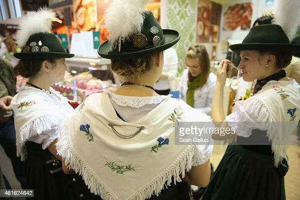 Women wearing folk costumes from the Allgaeu region of southern Bavaria sample food at a Slovenian stand at the International Green Week agricultural...