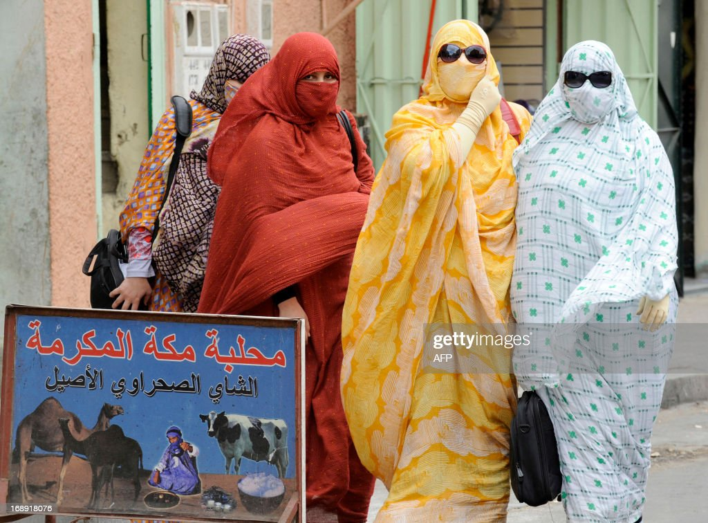 Women wearing full cover niqab and trendy sun glasses walk in a street of Laayoune, the capial of Moroccan-controlled Western Sahara on May 14, 2013. The Western Sahara is a highly sensitive subject in Morocco, which annexed the former Spanish colony in 1975 in a move never recognised by the international community. SENNA