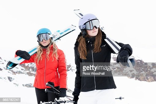Women wearing helmets and ski goggles holding skis, portrait