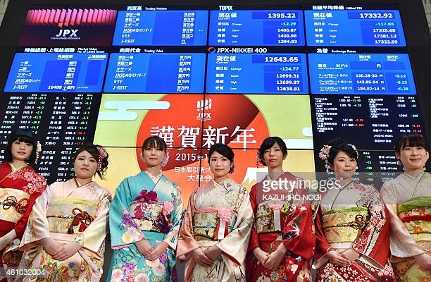 Women wearing kimonos pose in front of a quotation board at the opening ceremony of the first trading day of the year at the Tokyo Stock Exchange on...